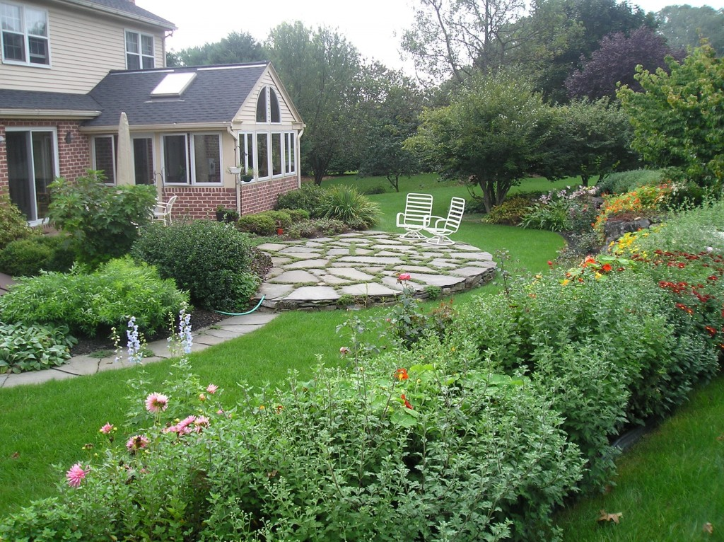 The stone walkway and patio break up the dense plantings.