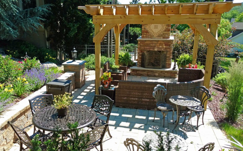 An outdoor fireplace on a Techo-bloc paver patio with a wood pergola by Lehigh Valley Landscape Company. Landscaping flowers and shrubs with patio furniture